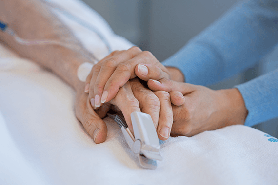 An elderly person has their hand held in hospital