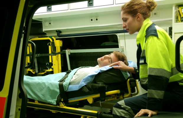Paramedic in ambulance with a patient on a stretcher