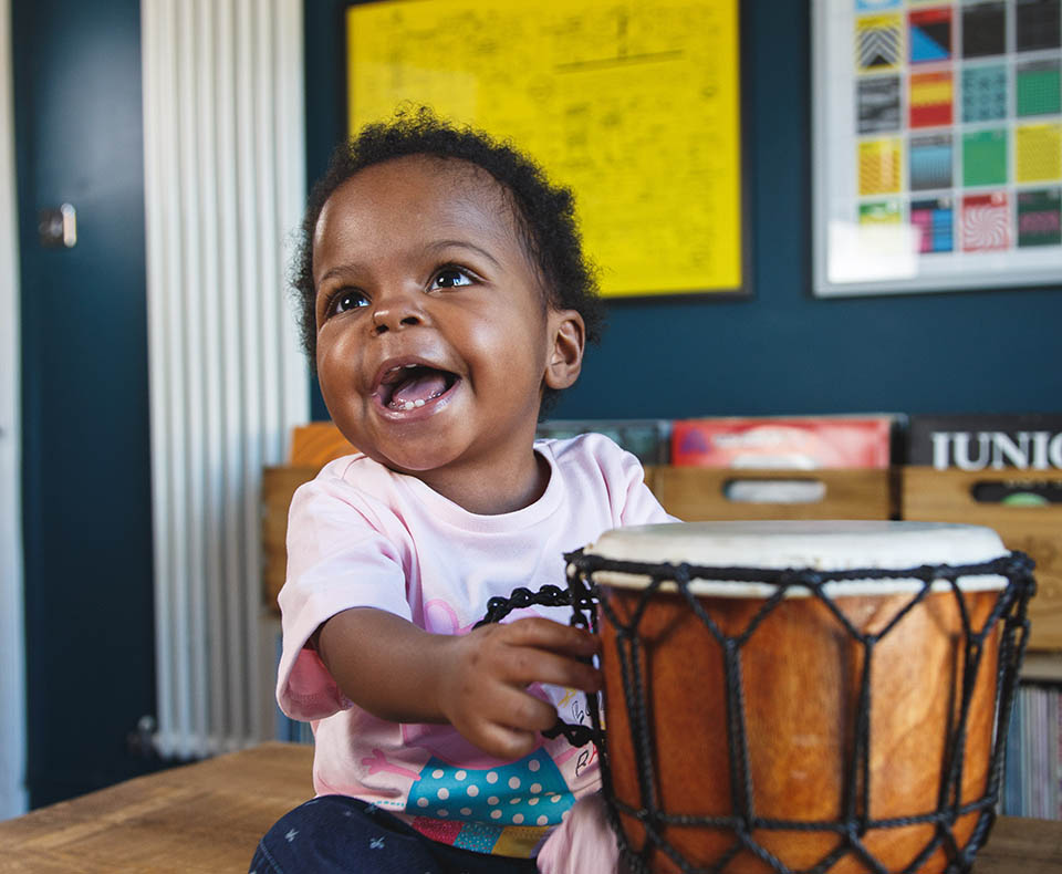 Baby Beau laughing and holding a drum.
