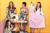 Four women standing around a sewing machine holding their upcycled items of clothing