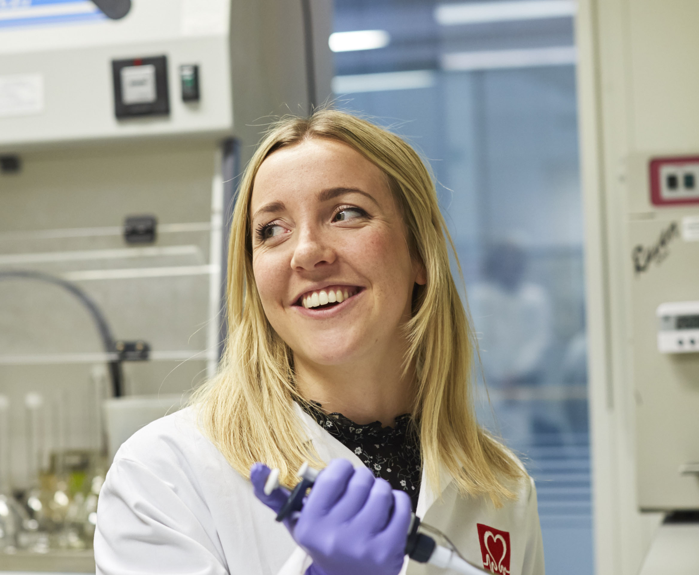 Researcher Alice Francis wearing a white coat and holding a syringe