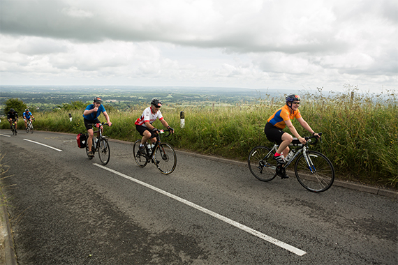 Three cyclists training on a country road