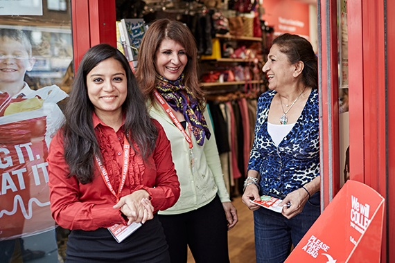 Three volunteers standing in a BHF shop entrance