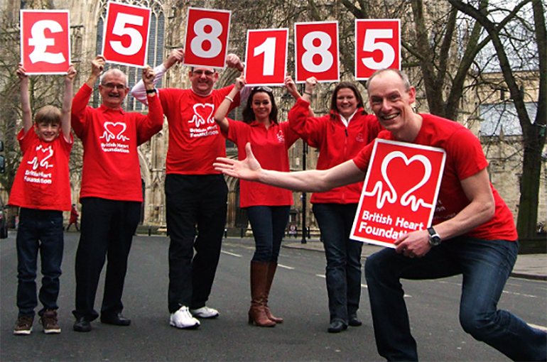 Group of volunteers holding cards to illustrate they have raised £58,185 for the BHF