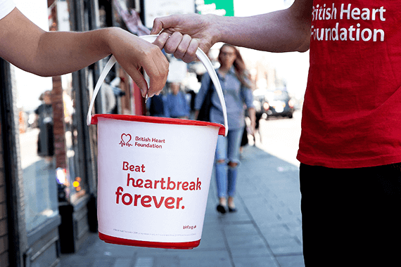 Staff stand in the high street with a BHF fundraising bucket