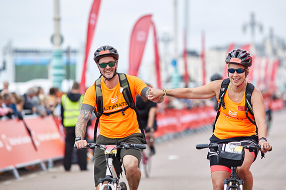A couple of riders successfully cross the finish line at our London to Brighton cycling event