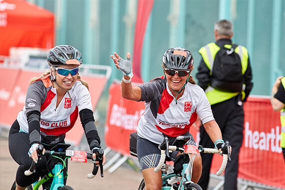 A couple of 700 club members wave at the crowd as they cross the line at the infamous London to Brighton bike ride - a BHF flagship fundraising event