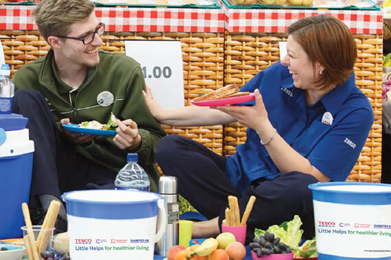 A couple of Tesco workers collect donations for the National charity partnership