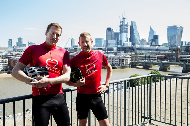 (L-R) Wilf and George Frost in cycling tops, holding helmets, in front of London city skyline