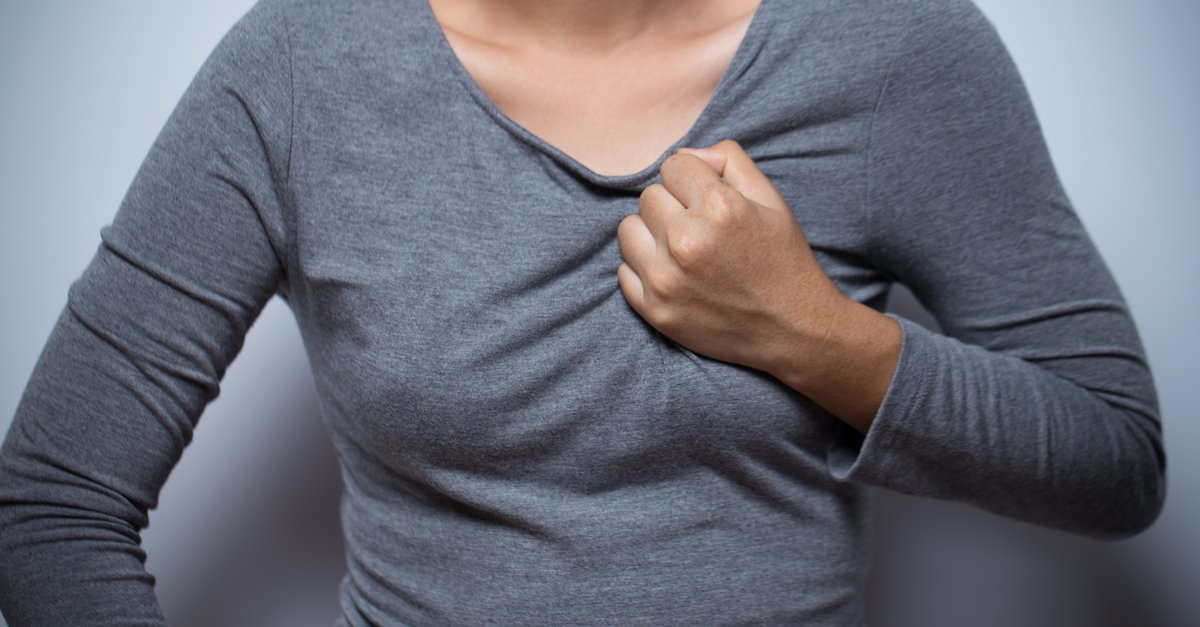Woman clutching chest, possible heart attack