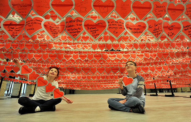 Two children affected by heart disease sit under a display of the love notes in the world record attempt