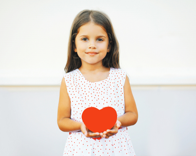 a portrait photograph of a young child holding a stylised heart in her hands