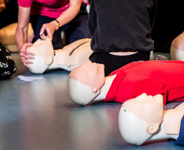 School children learning CPR