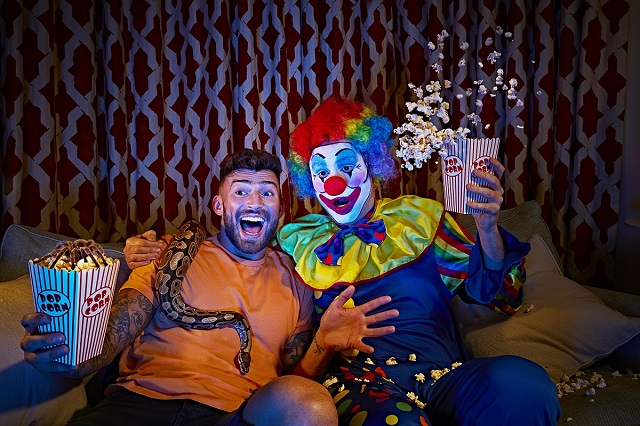 Jake Quickenden with a snake climbing over his shoulder watching a movie with a clown