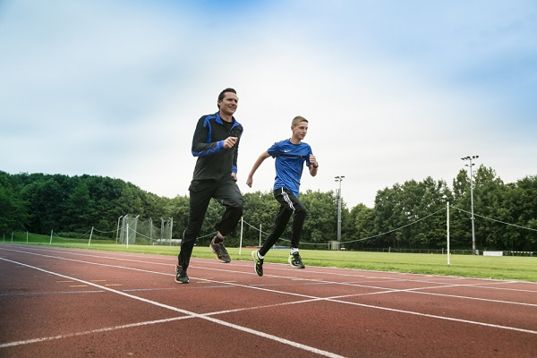 Roger Black and Luke Ball running on an athletics track