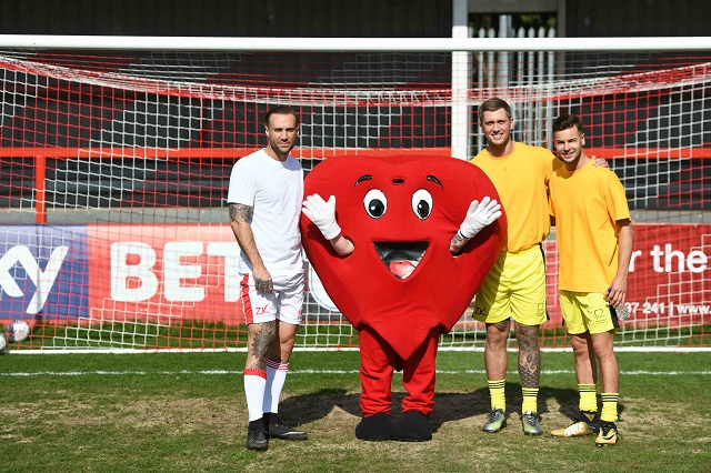 calum best, dan osbourne and chris hughes with Mr Hearty in front of a football goal
