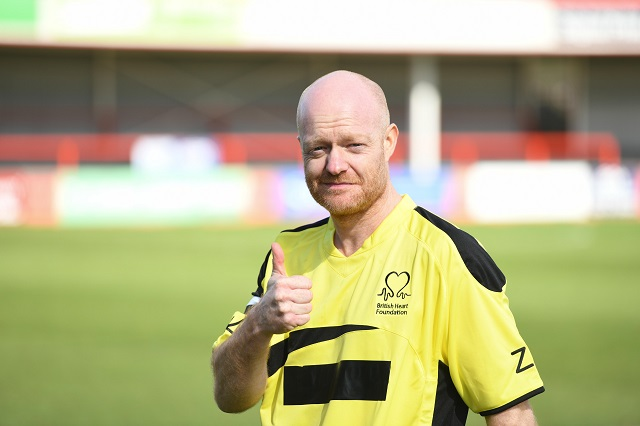jake wood with his thumb up on football pitch