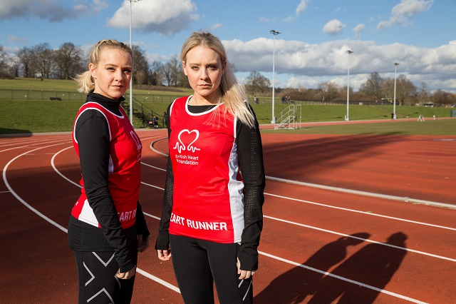 two girls in running vests staring into camera on running track