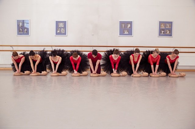 students at a ballet school pose learn CPR