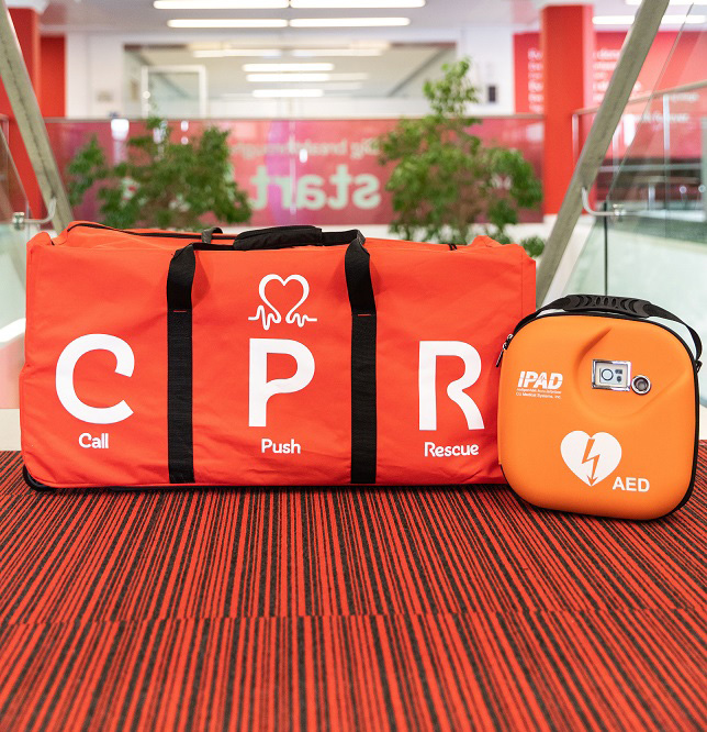 A bag with the letters CPR on the side next to a defibrillator.