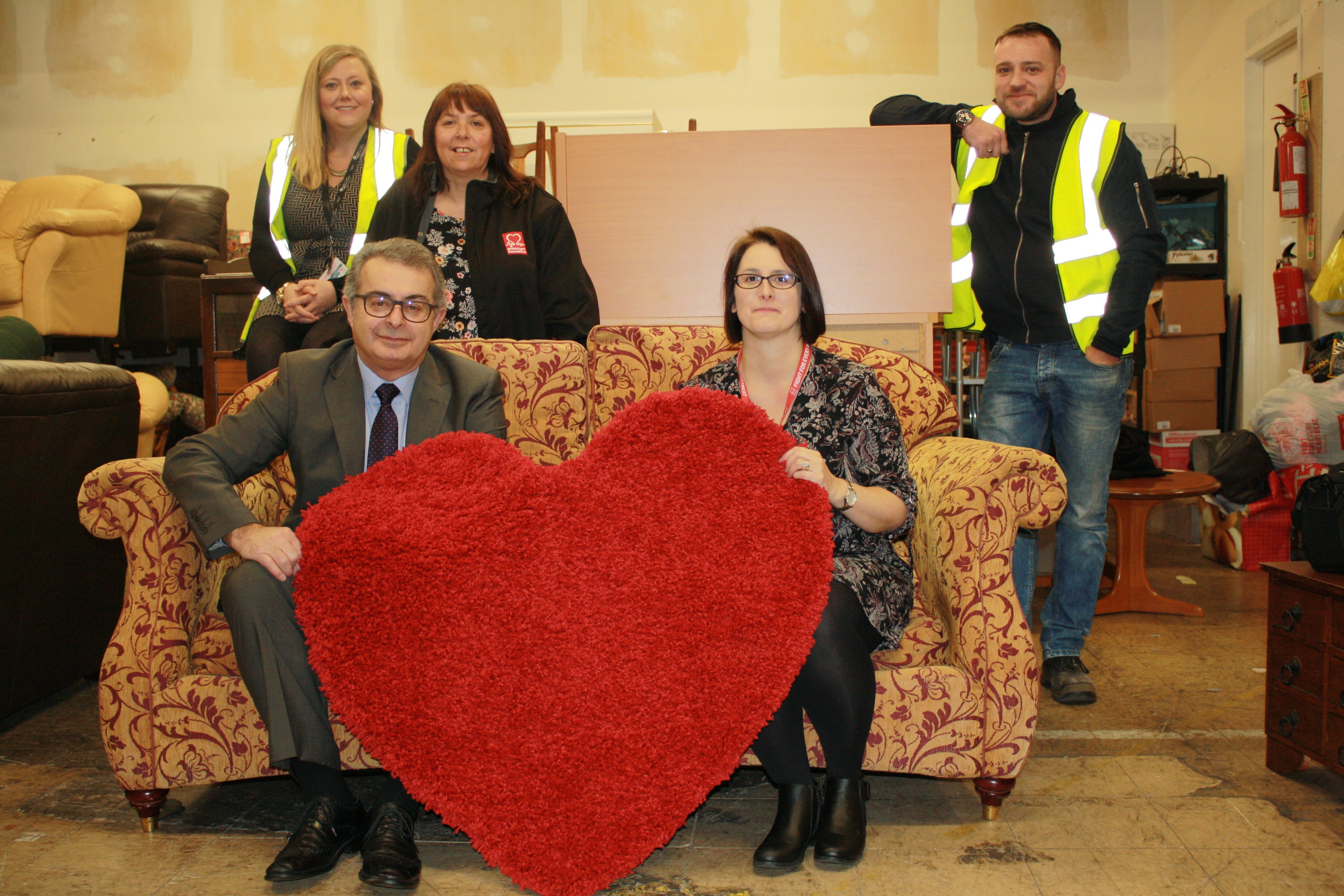 BHF Representatives and Cardiff Council in the Cardiff BHF Furniture & Electrical Store launching the Waste Reuse Partnership with a heart rug