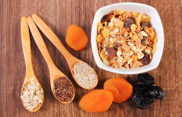 Apricot muesli on a bowl with three wooden spoons with ingredients